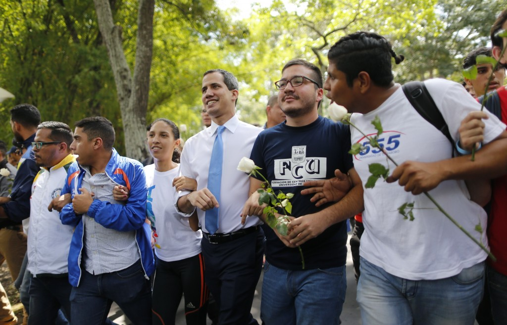 Venezuelan opposition leader, and self-proclaimed interim president of Venezuela, Juan Guaido, center, walks with students at the Central University o...