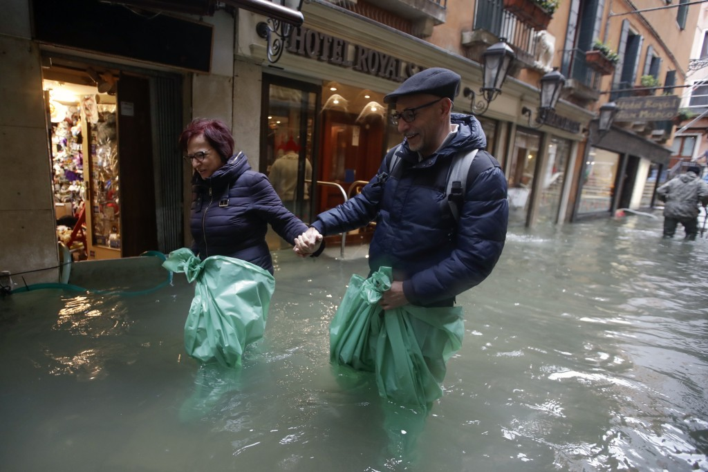 A couple wades their way through water in Venice, Italy, Friday, Nov. 15, 2019. Waters are rising in Venice where the tide is reaching exceptional lev...