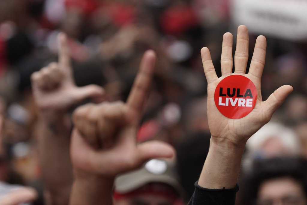 In this Saturday, Nov. 9, 2019 photo, a supporter of former Brazilian President Luiz Inacio Lula da Silva holds up his hand with a sticker that reads ...
