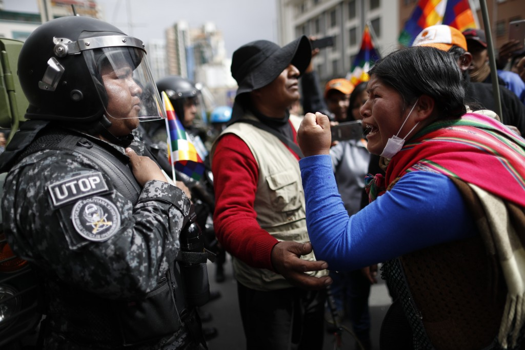 In this Tuesday, Nov. 12, 2019 photo, a supporter of Bolivia's former President Evo Morales yells at a police officer, telling him to respect the nati...