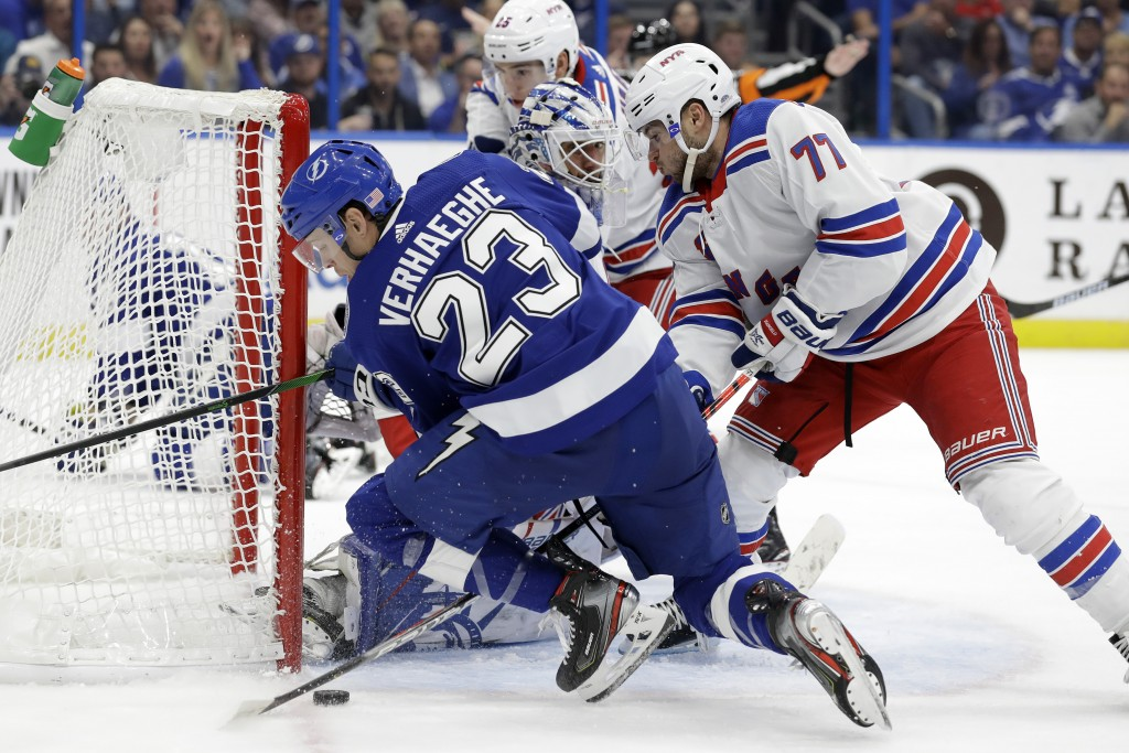 Tampa Bay Lightning center Carter Verhaeghe (23) gets knocked down by New York Rangers defenseman Tony DeAngelo (77) during the second period of an NH...