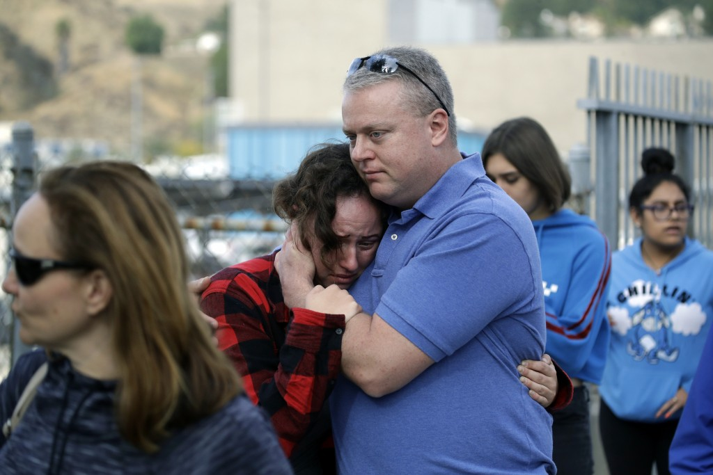Students are escorted out of Saugus High School as some parents join them after reports of a shooting on Thursday, Nov. 14, 2019, in Santa Clarita, Ca...