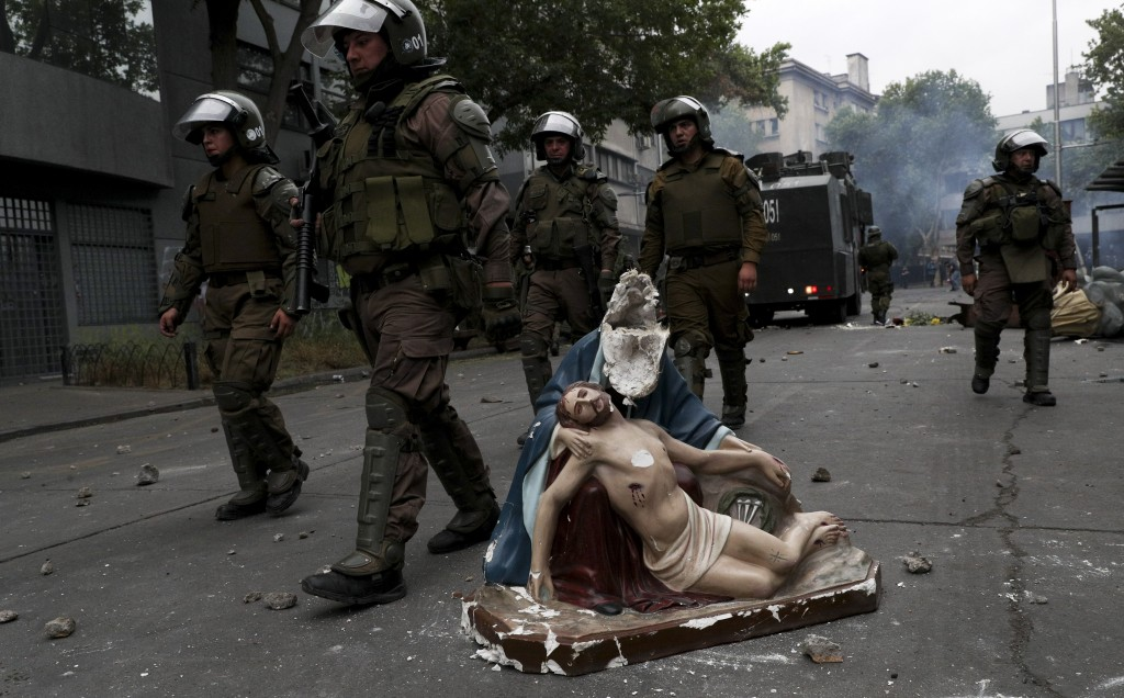 In this Friday, Nov. 8, 2019 photo, police advance on anti-government protesters, past a religious statue that protesters removed from a church and th...