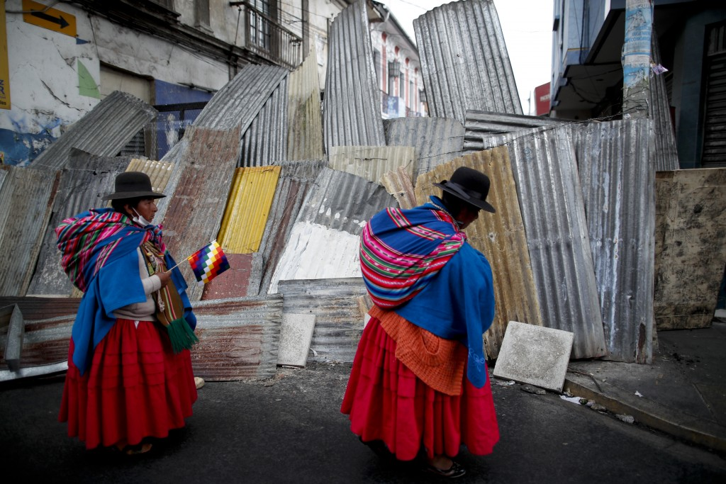 Supporters of former President Evo Morales stand at a barricaded stretch leading to the presidential palace during a march in La Paz, Bolivia, Thursda...