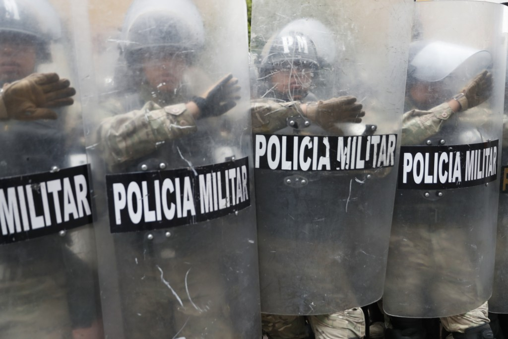 Police take cover behind their shields during a march of supporters of former President Evo Morales in La Paz, Bolivia, Thursday, Nov. 14, 2019. Moral...