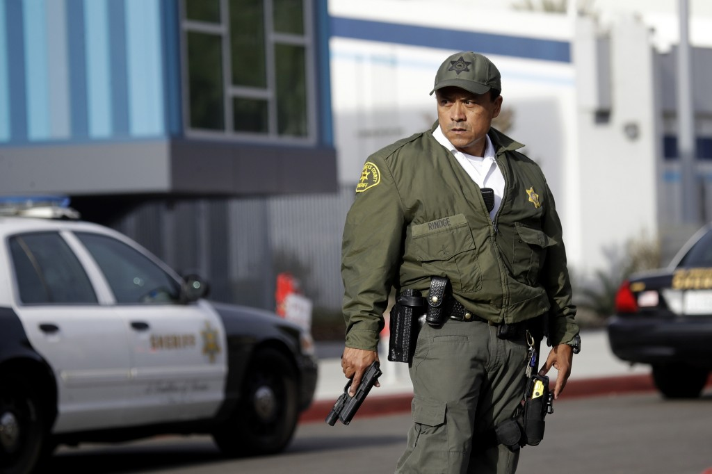 A member of the Los Angeles County Sheriff Department stands outside of Saugus High School with his weapon drawn after reports of a shooting on Thursd...