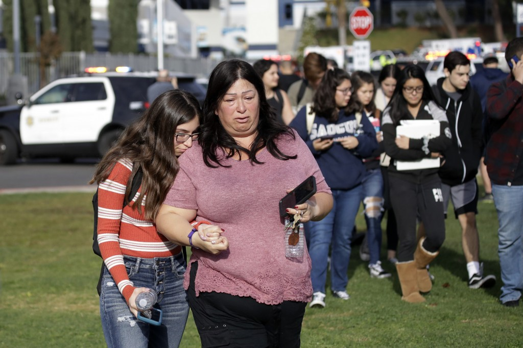 Students are escorted in a single file line as some parents pick them up outside of Saugus High School after reports of a shooting on Thursday, Nov. 1...