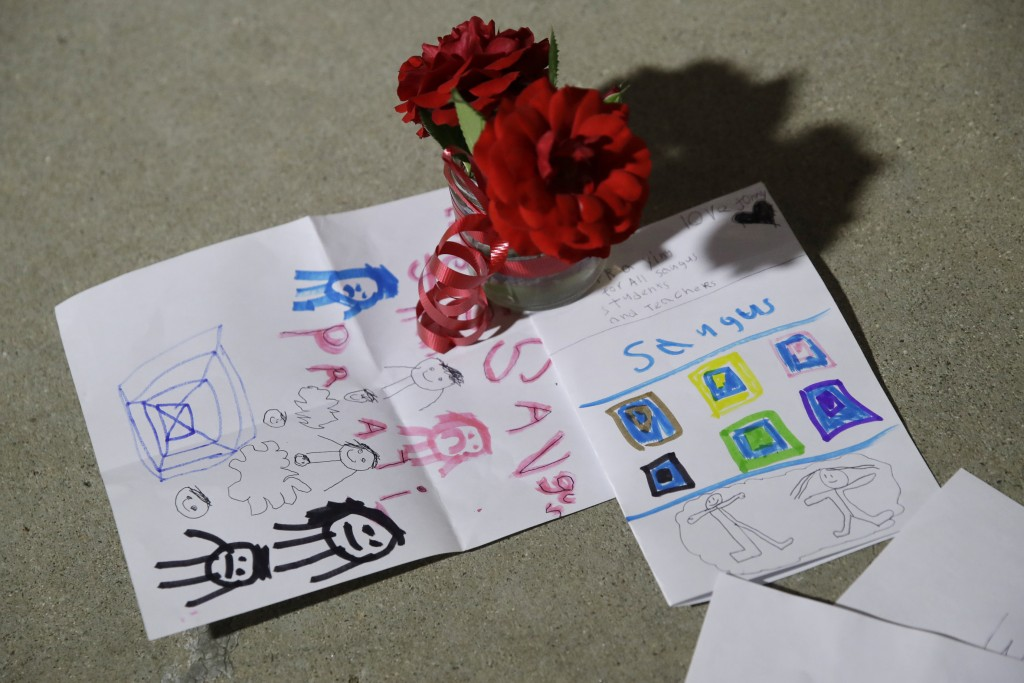 Flowers and cards are placed in front of Saugus High School in the aftermath of a shooting on Thursday, Nov. 14, 2019, in Santa Clarita, Calif. (AP Ph...