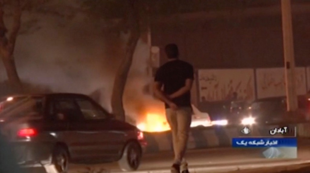 In this Saturday, Nov. 16, 2019 image from video aired by Iran's Islamic Republic of Iran Broadcasting state television channel, a man walks past a fi...