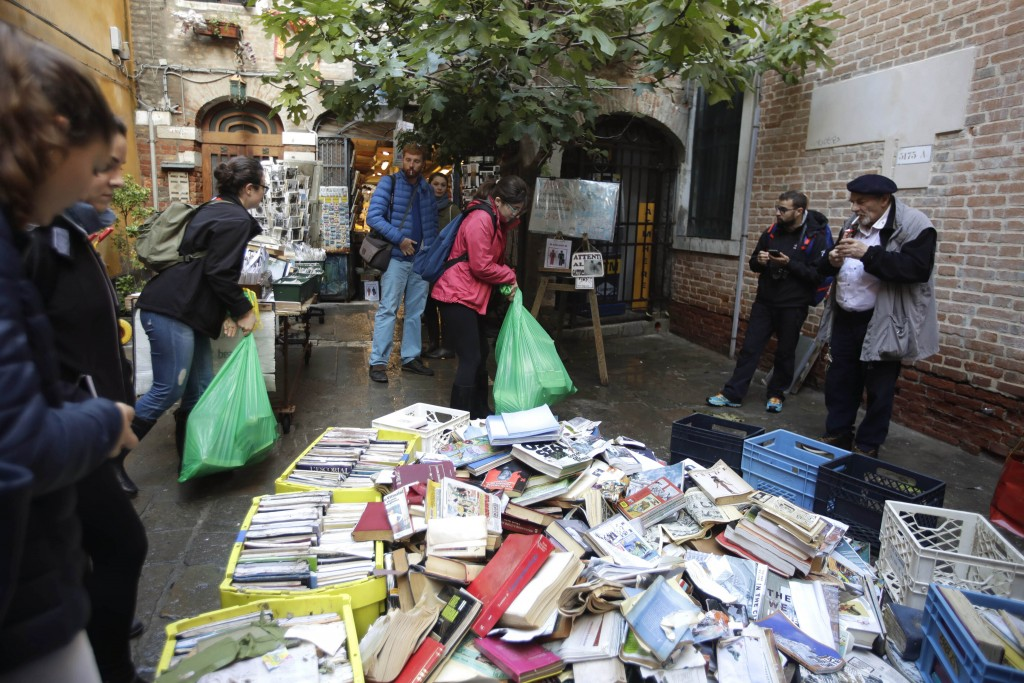"""Damaged books are piled outside renowned bookstore """"Acqua Alta"""" (High Water) as volunteers help cleaning after flooding in Venice, Italy, Saturday, No..."""