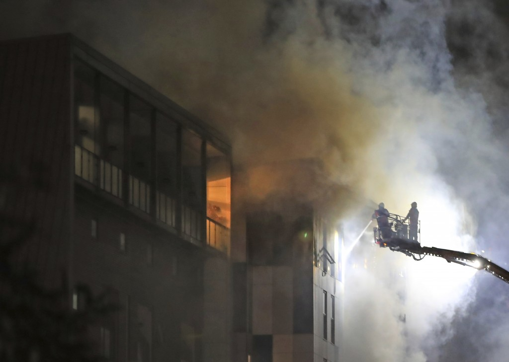 Fire fighters work at the scene of a major fire at a student residential building in Bolton, England, late Friday Nov. 15, 2019.  Fire crews tackled t...