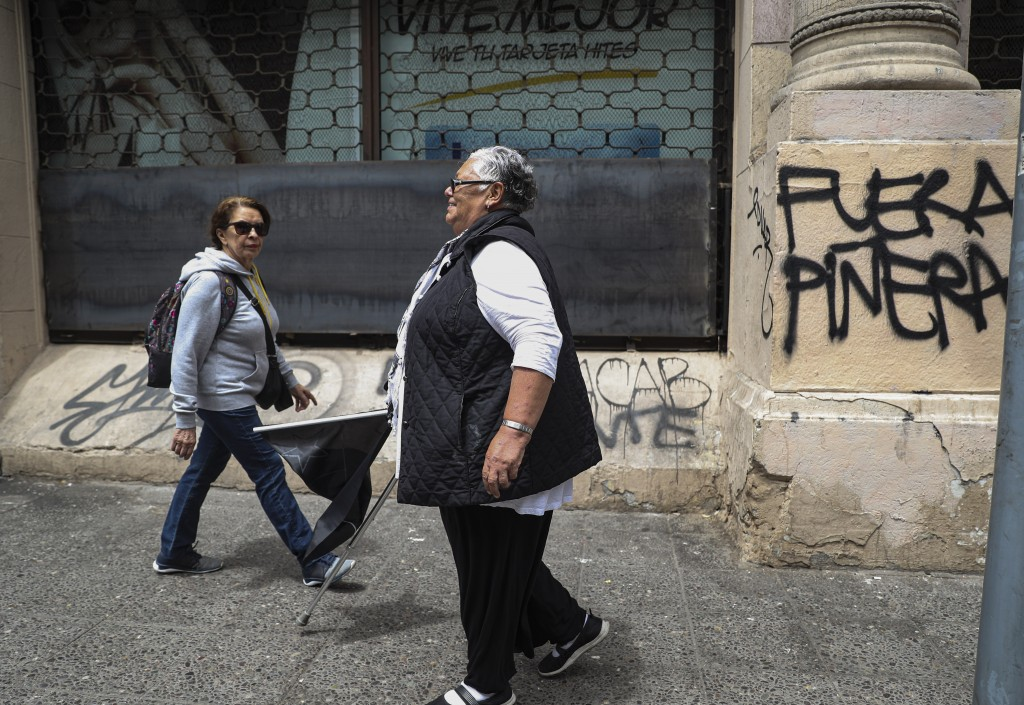 In this Nov. 4, 2019 photo, retired Magdalena Alvarez, 64, walks away after taking part in a protest against Chile's President Sebastian Pinera, in do...