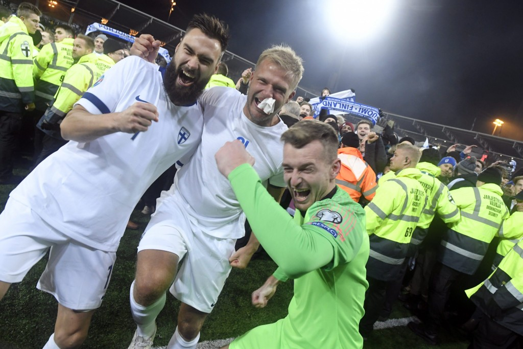 Finnish captain Tim Sparv, left, celebrates with Paulus Arajuuri, center, and goalkeeper Lukas Hradecky after their victory in the Euro 2020 Group J q...