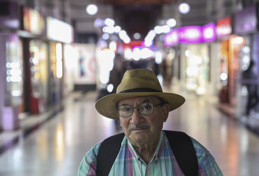 In this Nov. 5, 2019 photo, retired Nestor Osorio, 66, poses for a photo after a day of work in downtown Santiago, Chile. What started on Oct. 18 as a...
