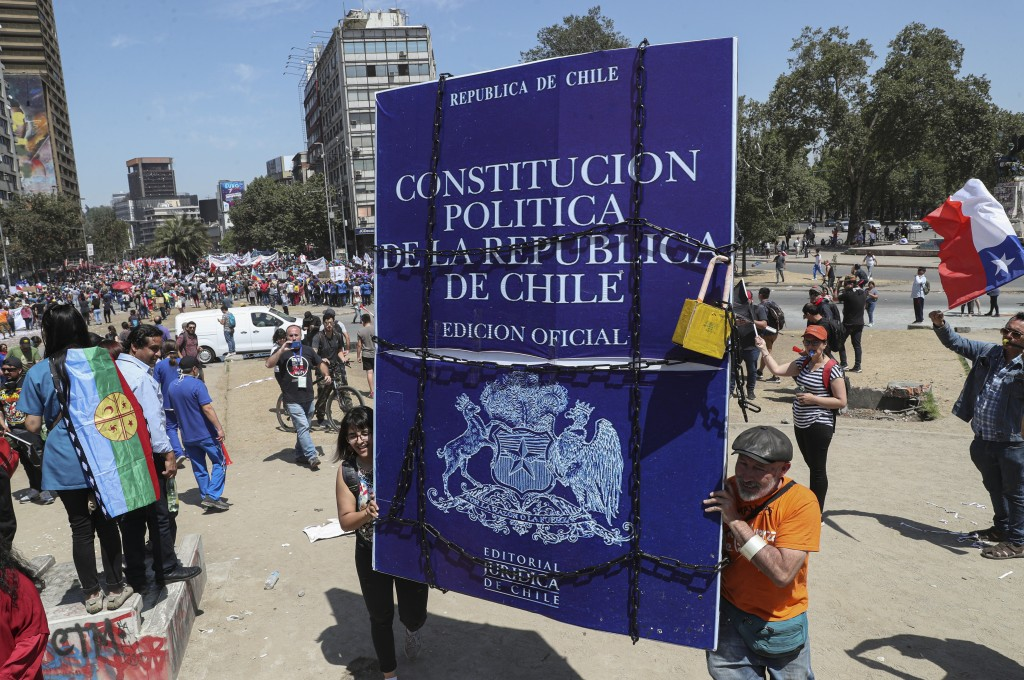 In this Nov. 12, 2019 photo, anti-government demonstrators carry a sign representing Chile's Constitution during protests, in Santiago, Chile. In 1981...