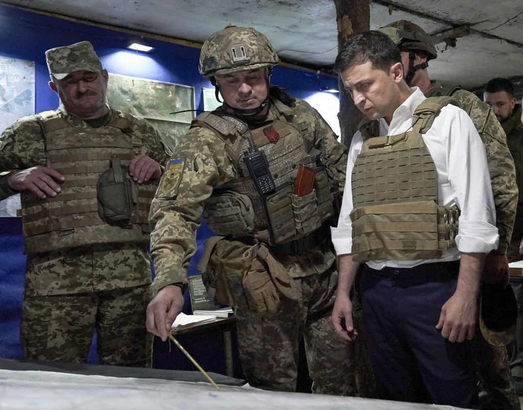 FILE - In this file photo taken on Oct. 14, 2019, Ukrainian President Volodymyr Zelenskiy, right, listens to a serviceman as he visits the war-hit Don...