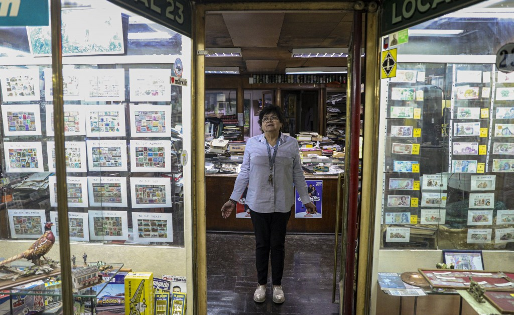 In this Nov. 4, 2019 photo, retired Rosa Lara, 74, poses for a photo inside a philately store in downtown of Santiago, Chile. The protests in Chile in...