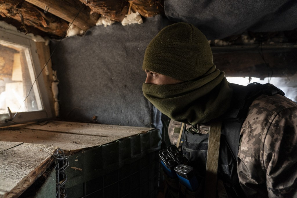 FILE - In this Nov. 2, 2019, file photo a Ukrainian serviceman watches from his position at the new line of contact in Zolote, Luhansk region, eastern...