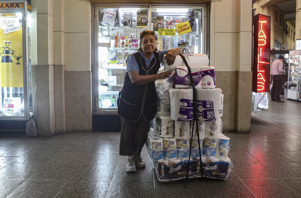 In this Nov. 5, 2019 photo, retired Maria Gonzalez, 77, poses for a photo as she takes a break from selling tissue and toilet paper in downtown Santia...