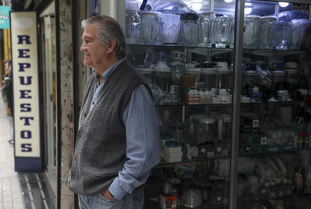 In this Nov. 4, 2019 photo, retired Jose Urzua, 74, poses for a photo at his work at a store that sells spare parts for blenders, in downtown Santiago...