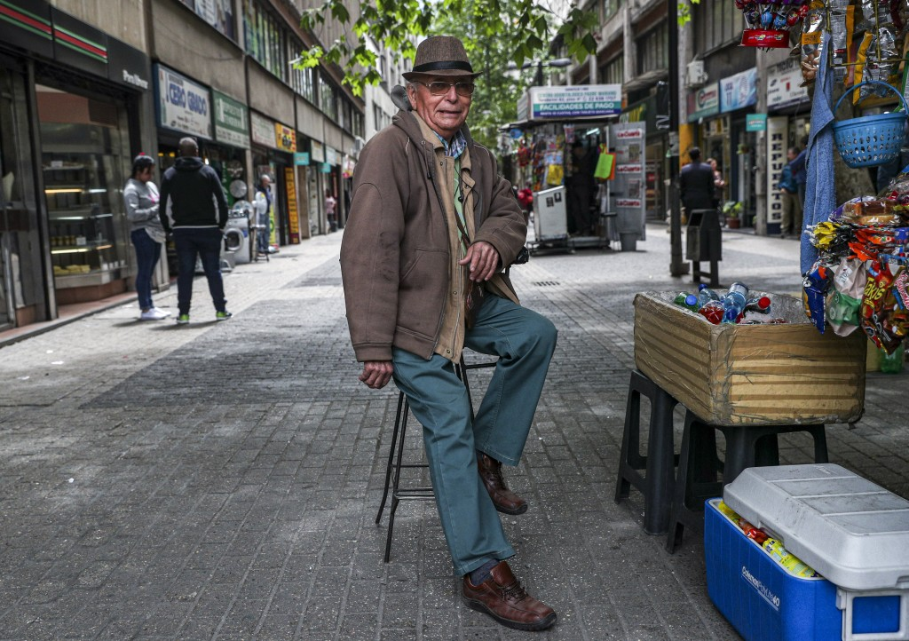 In this Nov. 4, 2019 photo, retired Emilio Monardes, 78, works as a street merchant in downtown Santiago, Chile. More than 1.2-million Chileans receiv...