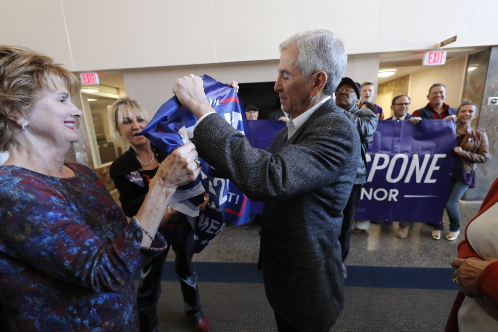 Louisiana Republican gubernatorial candidate Eddie Rispone signs a campaign banner as he greets supporters at a campaign stop in Shreveport, La., Frid...