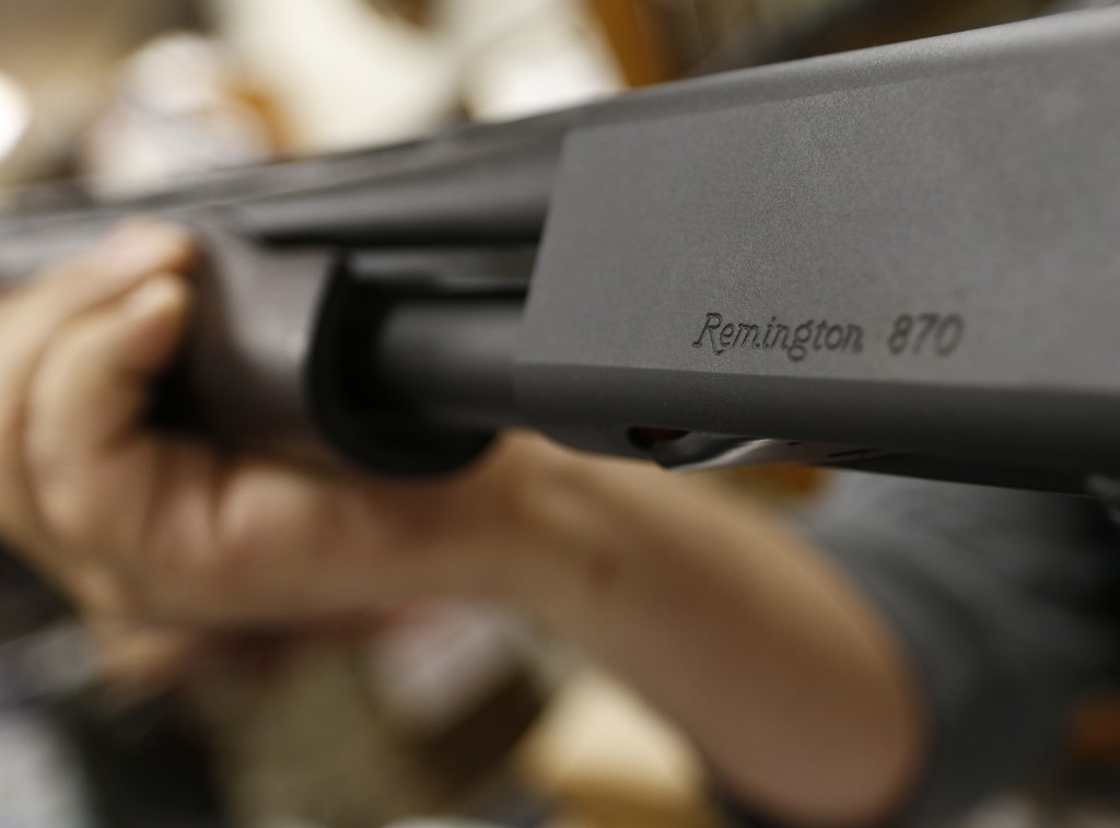 FILE - In this March 1, 2018 file photo, the Remington name is seen etched on a model 870 shotgun at Duke's Sport Shop in New Castle, Pa. For years, t...