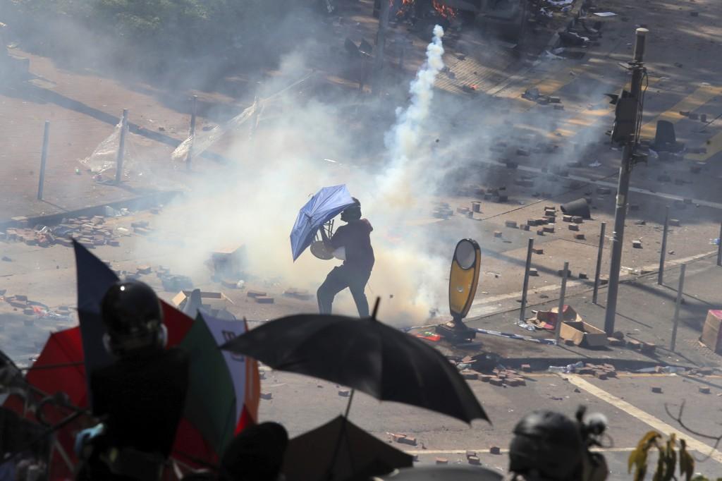 A protestor reacts as police fire tear gas at Hong Kong Polytechnic University in Hong Kong, Sunday, Nov. 17, 2019. (AP Photo/Kin Cheung)
