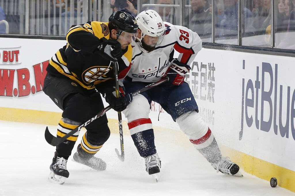 Boston Bruins' Paul Carey (34) and Washington Capitals' Radko Gudas (33) vie for the puck during the first period of an NHL hockey game in Boston, Sat...