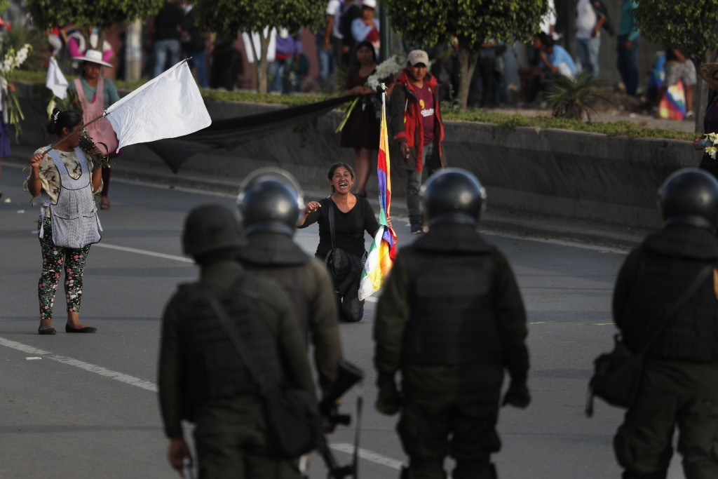 A coca leaf producer kneels leads with police to open the way so a march by backers of former President Evo Morales may continue to Cochabamba, Bolivi...