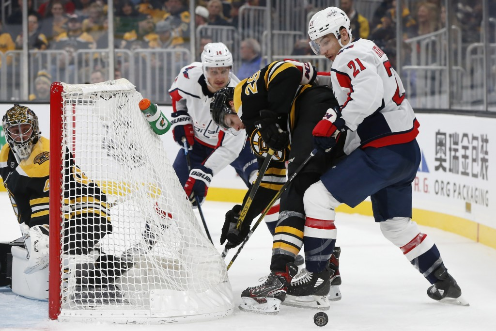 Washington Capitals' Garnet Hathaway (21) and Boston Bruins' Brandon Carlo (25) work for the puck during the second period of an NHL hockey game in Bo...