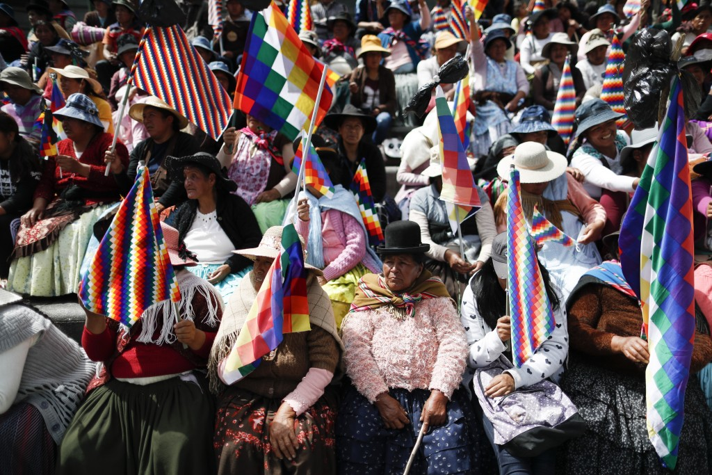 "Women, holding the multicolor ""Wiphala"" flag that represents indigenous peoples, take part in a meeting of backers of former President Evo Morales to ..."