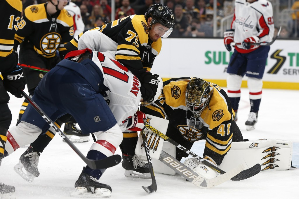 Boston Bruins' Jaroslav Halak (41) covers the puck as Connor Clifton (75) defends against Washington Capitals' Garnet Hathaway (21) during the second ...