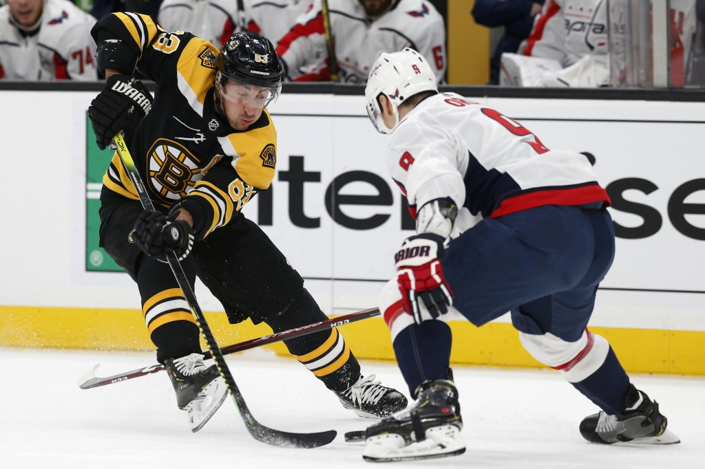 Washington Capitals' Dmitry Orlov (9) defends against Boston Bruins' Brad Marchand (63) during the first period of an NHL hockey game in Boston, Satur...