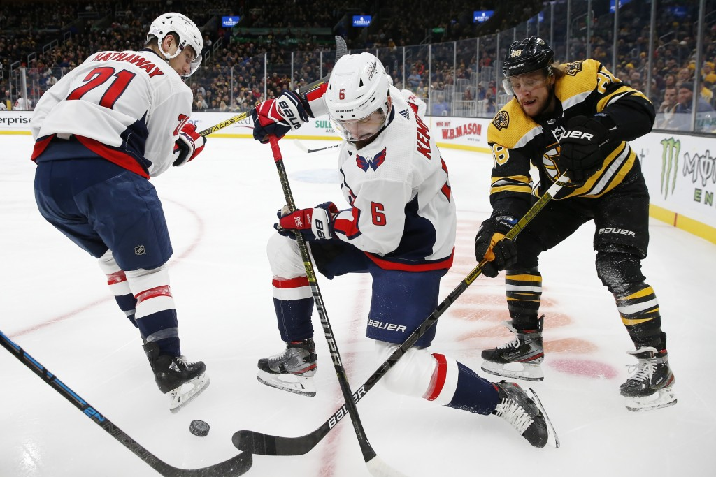 Boston Bruins' David Pastrnak (88) competes against Washington Capitals' Michal Kempny (6) for the puck during the first period of an NHL hockey game ...