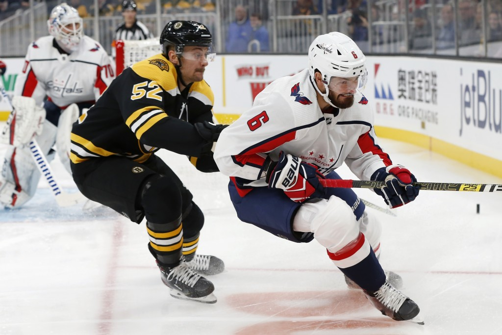 Boston Bruins' Sean Kuraly (52) defends against Washington Capitals' Michal Kempny (6) during the first period of an NHL hockey game in Boston, Saturd...