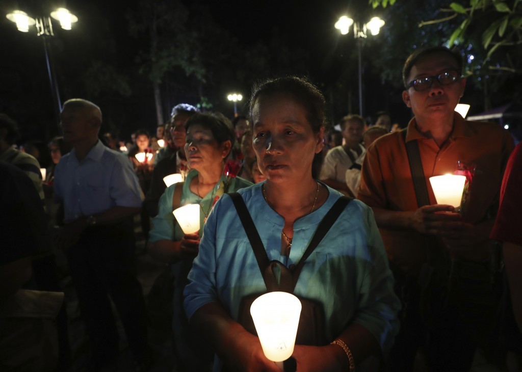 In this Friday, Oct. 18, 2019, photo, Catholic devotees hold candles during the 30th anniversary of the beatification of seven martyrs at Songkhon vil...