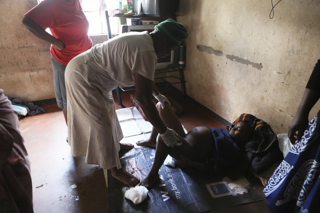 72-year old grandmother Esther Zinyoro Gwena, left, attends to a woman in labor in her tiny apartment in the poor surburb of Mbare in Harare, Zimbabwe...