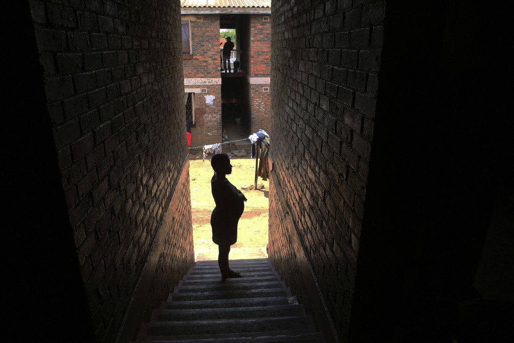 A pregnant woman waits in a passageway, waiting for her turn to deliver her baby, in a tiny apartment in the poor surburb of Mbare in Harare, Zimbabwe...