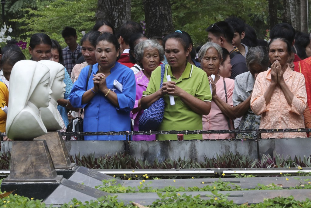 In this Saturday, Oct. 19, 2019, photo, Catholic devotees pray at the busts of Agnes Phila,  front, and Lucia Khambang, two of seven martyrs at the ce...