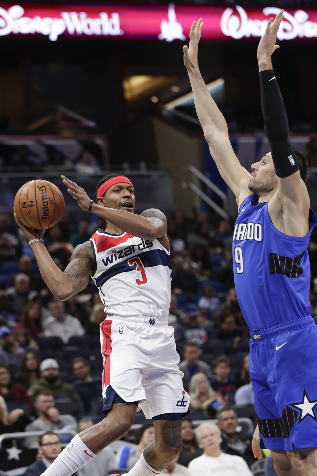 Washington Wizards' Bradley Beal (3) passes the ball around Orlando Magic's Nikola Vucevic (9) during the first half of an NBA basketball game, Sunday...