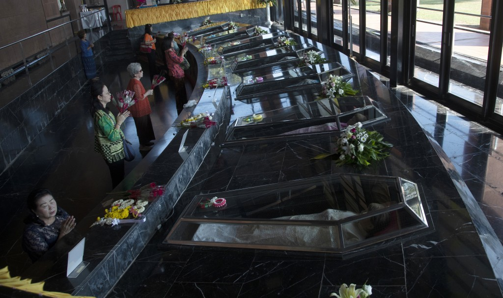 In this Saturday, Oct. 19, 2019, photo, Catholic devotees pray in front of glass caskets containing the seven replicas of the Blessed Martyrs at Chris...
