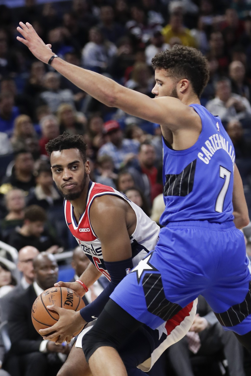 Washington Wizards' Troy Brown Jr., left, looks to make a move around Orlando Magic's Michael Carter-Williams (7) during the first half of an NBA bask...