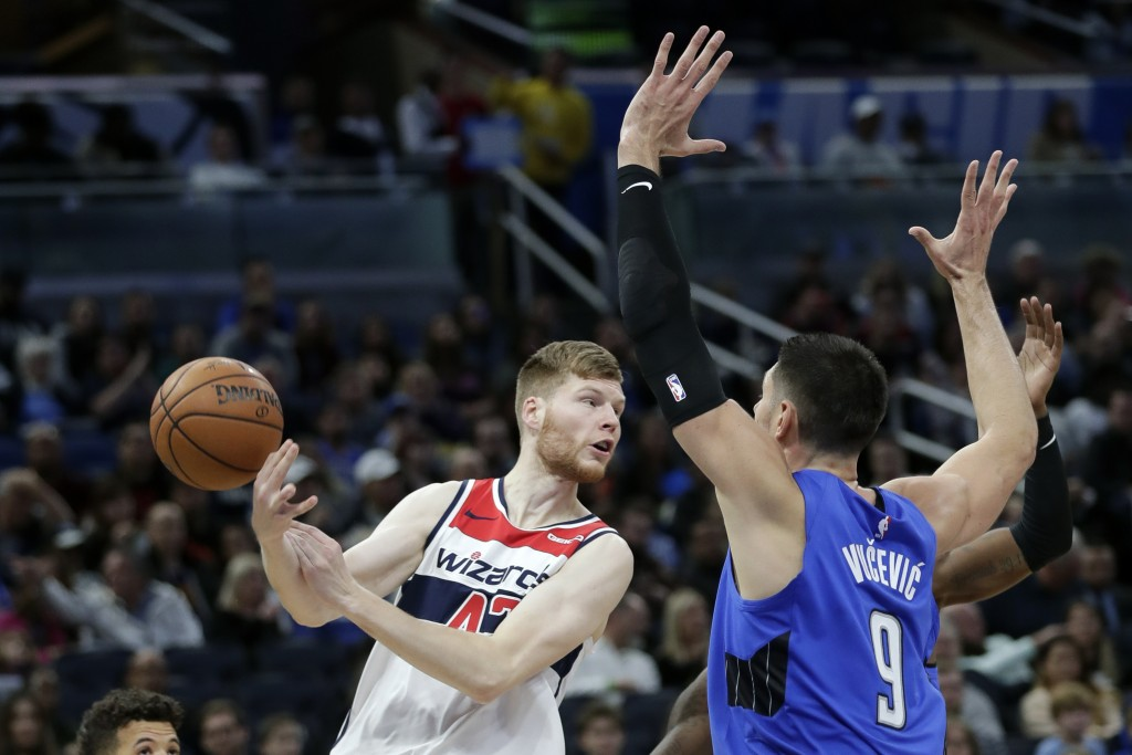 Washington Wizards' Davis Bertans, left, loses control of the ball as he tries to pass over Orlando Magic's Nikola Vucevic (9) during the first half o...