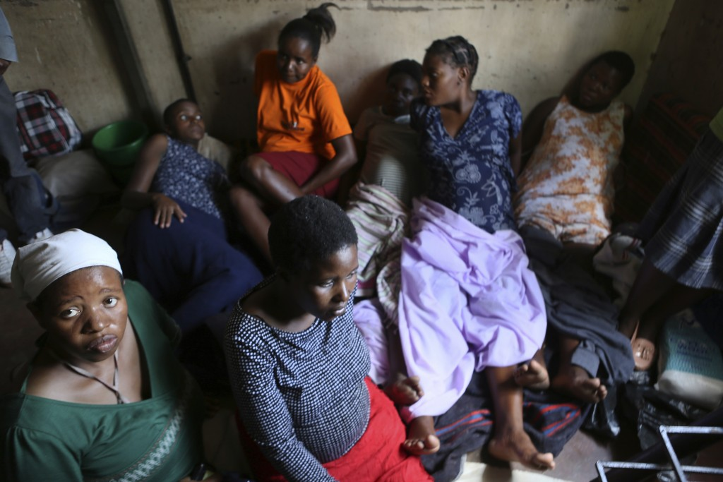 Women wait for their turn to deliver their babies, in a cramped apartment in the poor suburb of Mbare in Harare, Zimbabwe, Saturday, Nov. 16, 2019, wi...
