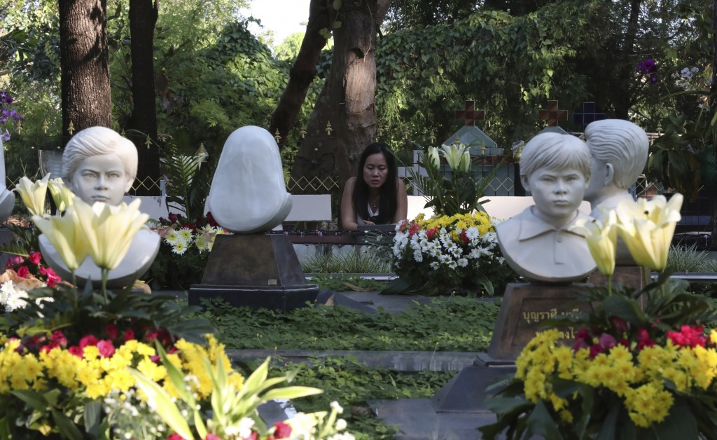 In this Friday, Oct. 18, 2019, photo, a Catholic devotee prays at the busts of Cecilia Butsiat, front left, and Maria Phon, front right, at the seven ...