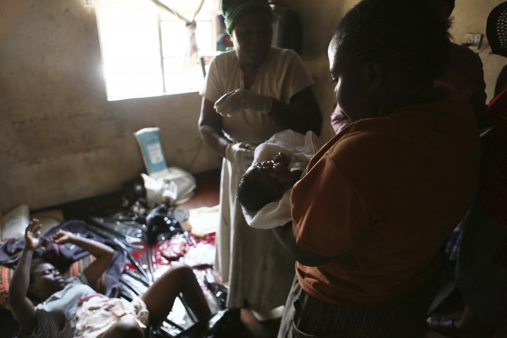 A woman holds a baby delivered in a tiny apartment in the poor suburb of Mbare in Harare, Zimbabwe, Saturday, Nov. 16, 2019, after the baby was delive...