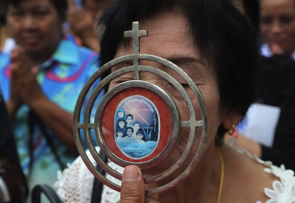 In this Saturday, Oct. 19, 2019, photo, a Catholic devotee kisses a sacramental with an image of the seven martyrs at cemetery during the 30th anniver...