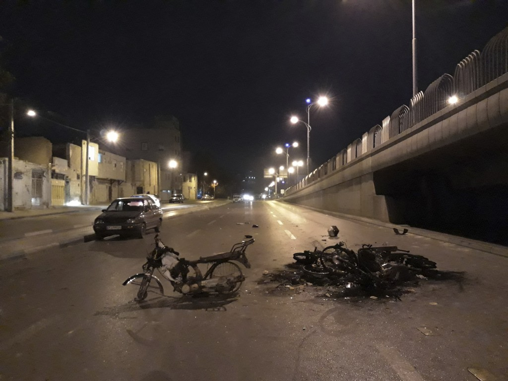 In this Saturday, Nov. 16, 2019 photo, released by Iranian Students' News Agency, ISNA, scorched motorcycles remain on the street after protests that ...