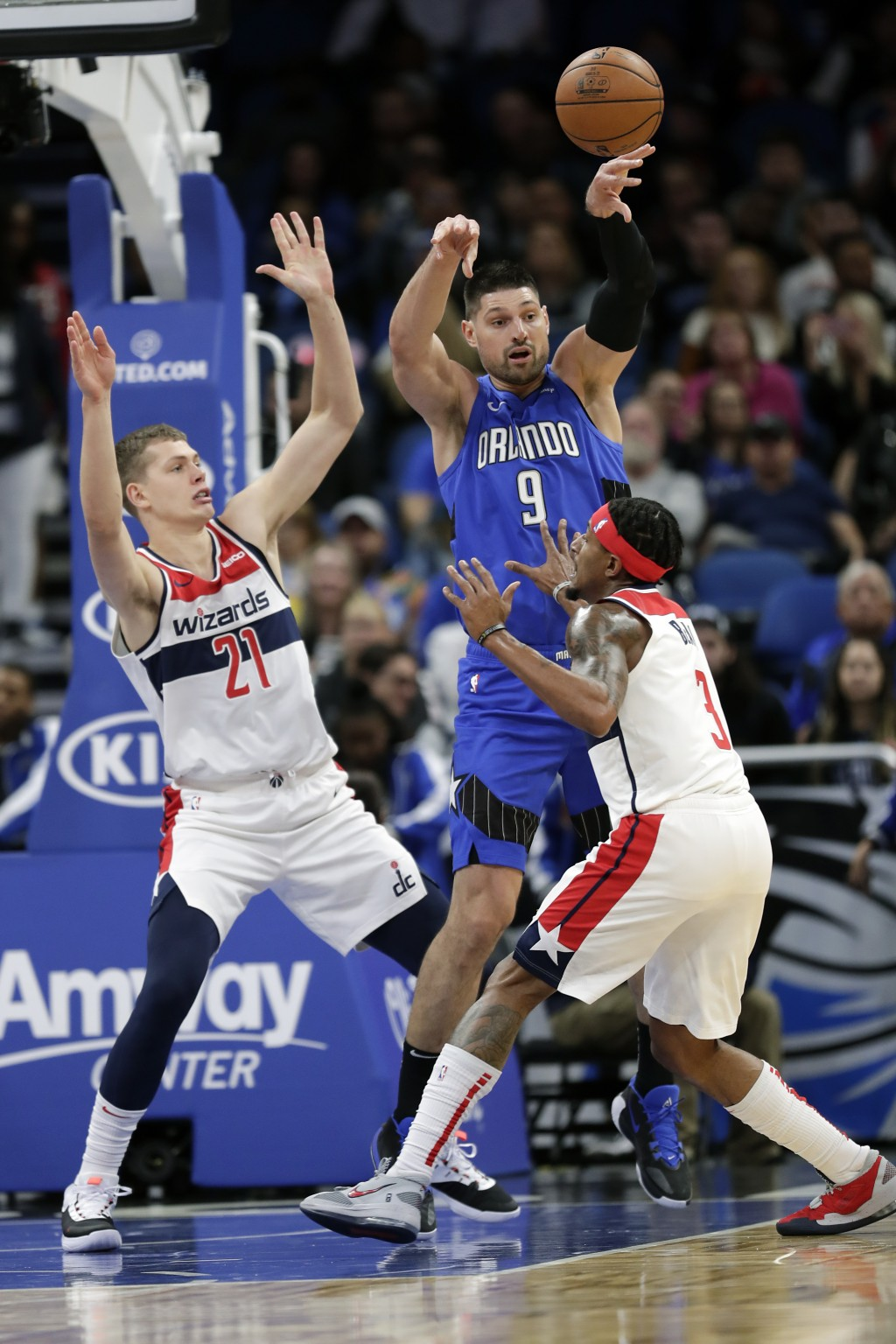 Orlando Magic's Nikola Vucevic (9) passes the ball out as he is boxed in by Washington Wizards' Moritz Wagner (21) and Bradley Beal, right, during the...